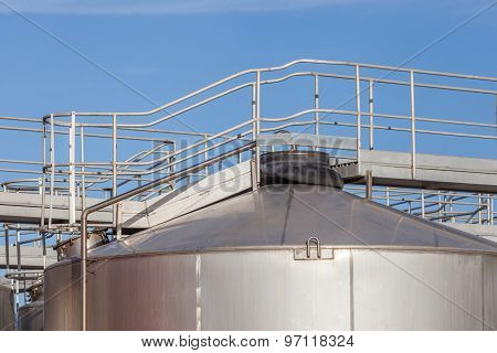 The Walkway On Top Of Big Industrial Tanks Farm In Refinery Industry.