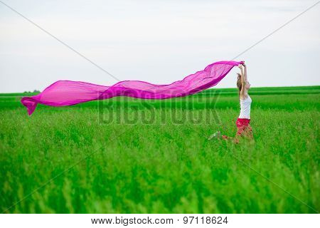 Young lady runing with tissue in green field. Woman and scarf.