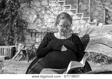 Pregnant Woman Reading Book Outdoors