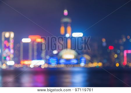Blurred bokeh lights background of Hong Kong city at night with water reflection