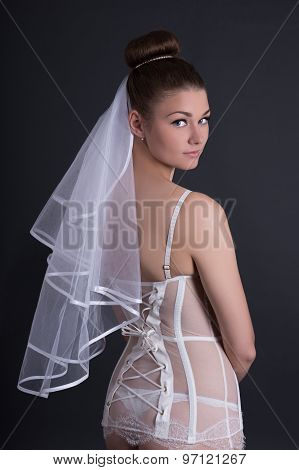 Pretty Woman In White Sexy Lingerie With Veil Over Grey