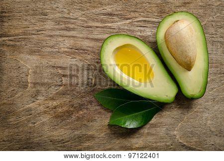 Fresh Avocado And Half Of Avocado Like A Bowl For Oil On Wooden Background