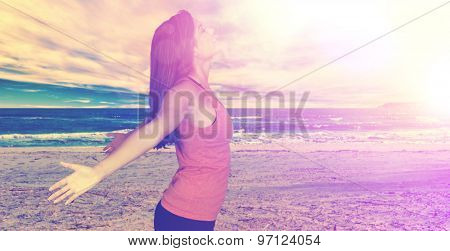 Woman working out doing yoga at the beach