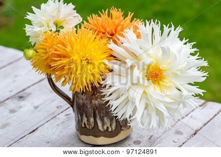 Bouquet of  home grown dahlias in a pottery pitcher.