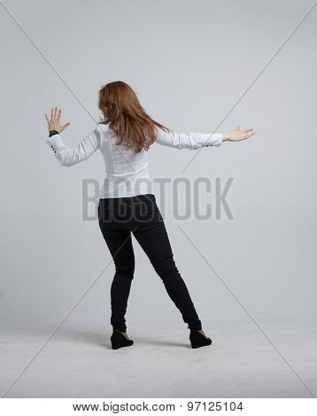 Young girl stands back and working with virtual screen on gray background