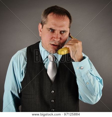 A serious business man is talking on a banana phone on an isolated gray background for a humor or communication concept.