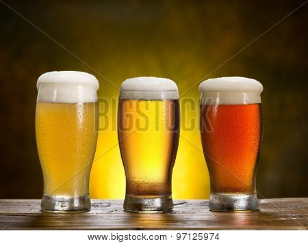 Three beer glasses on a wooden table.