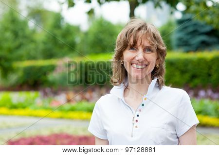 Smiling middle age woman portrait in a park