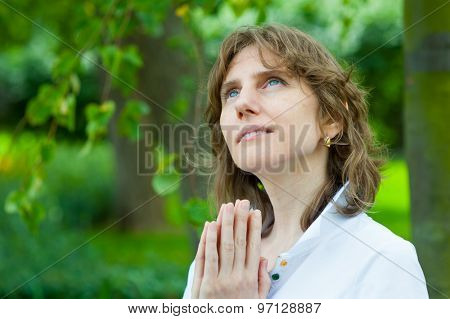 Smiling middle age woman praying in a park