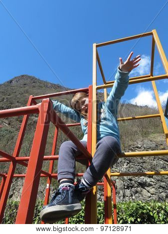Cute Little Girl Is Climbing  In Playground Equipment