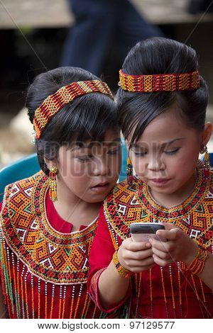 Portrait Of Two Young Torajan Girls with mobile phone