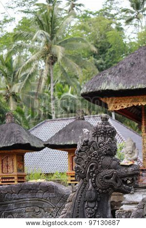 Balinese Statue With Traditional Architecture