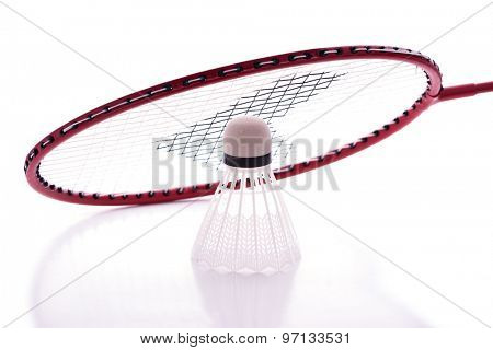 Badminton racket and shuttlecock with reflections against white background