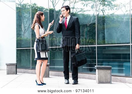 Asian business woman and man telephoning with mobile phone in front of building