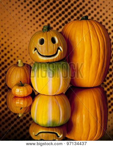 A variety of five stacked pumpkins and their reflection on a on an orange and black spotted background.  One pumpkin has happy carved face.