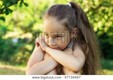 Closeup portrait of sad cute little girl at sunset. Domestic violence concept.