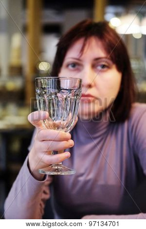 Woman holding an empty glass in the restaurant