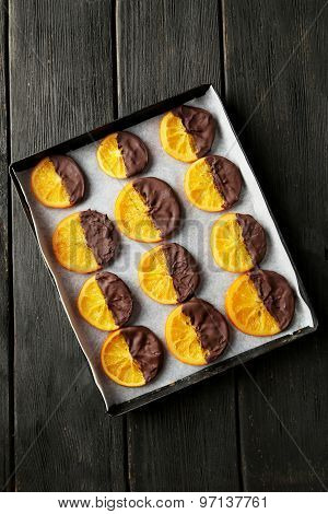Delicious slices of orange coated chocolate on pan