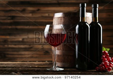 Glass of red wine with bottle on wooden table
