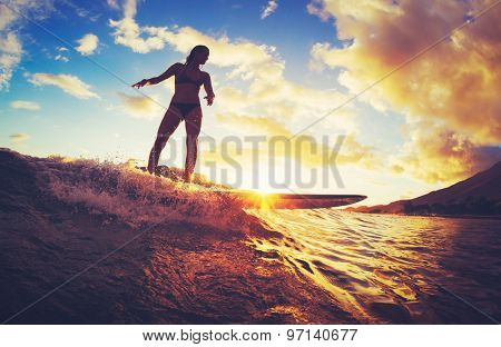 Surfing at Sunset. Beautiful Young Woman Riding Wave at Sunset. Outdoor Active Lifestyle.