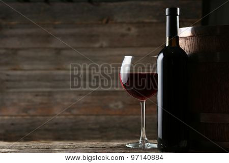Glass of wine on wooden background, on table