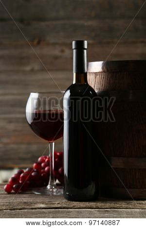 Glass of wine with fresh grapes on wooden table