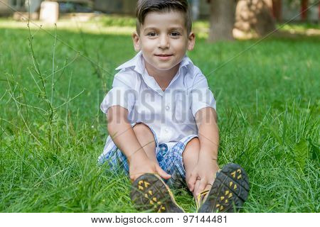 happy young child boy outdoor portrait on natural green background