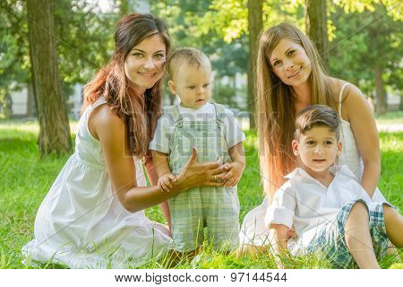 two young happy women with kids on natural green background, smiling happy girls with kids outdoor portrait
