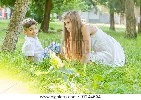 happy young mother with child - boy - outdoor portrait on green natural background
