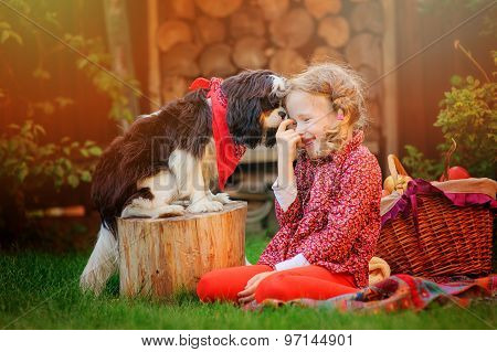 happy child girl playing with her cavalier king charles spaniel dog in autumn garden
