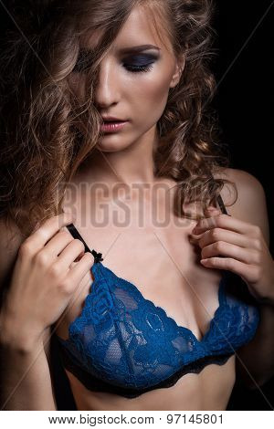 Sensual sexy brunette woman posing in a dark blue lace erotic lingerie