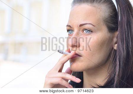 Closeup Of A Pretty Woman Smoking At The Street