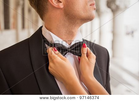 Lady fixing man's bow tie