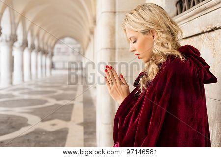 Woman in red cloak praying