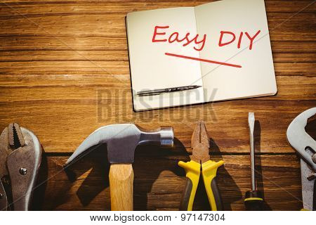 The word easy diy and notebook and pen against desk with tools