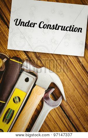 The word under construction and architect background against white card