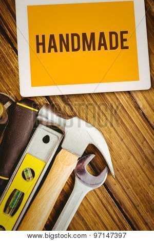 The word handmade and tablet pc against desk with tools