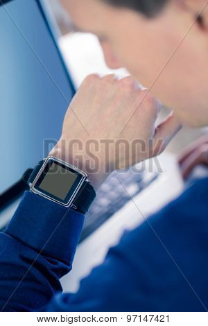 Rear view of businessman watching his smartwatch in his office