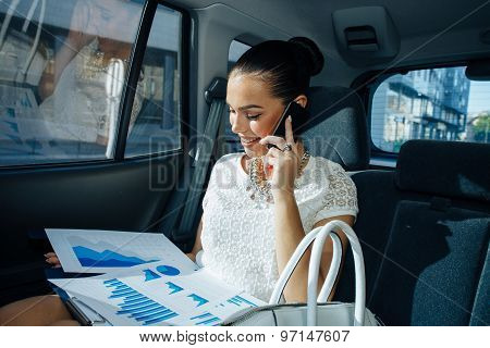 Young Businesswoman Talking On The Phone In The Back Seat Of The Car And Holding Document With Chart