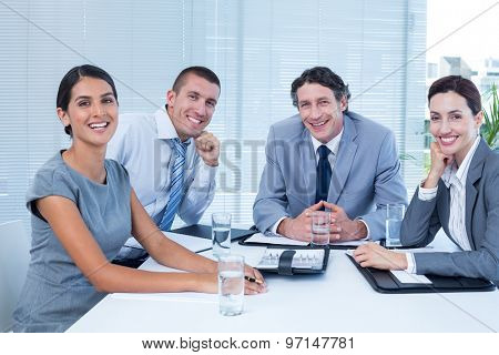 Smiling business team sitting at desk in the office