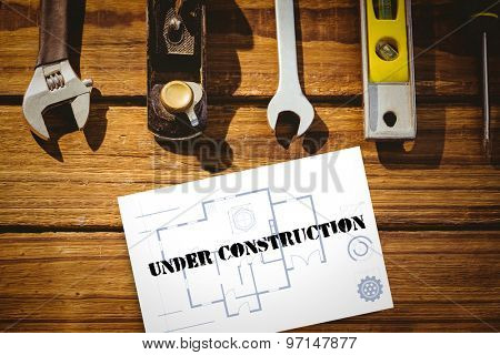 The word under construction and blueprint against white card