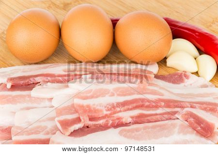 Pieces Of Bacon, Eggs And Peppers On Wooden Board