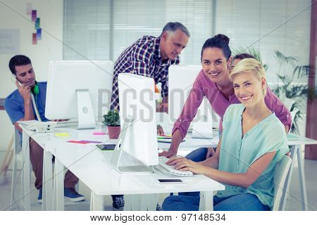 Side view of smiling photo editors using computer in the office