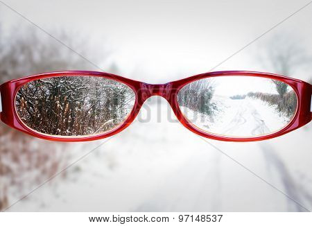 Glasses against winter road with snow