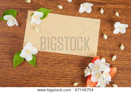 card on a wooden surface with jasmine flowers and strawberries. background