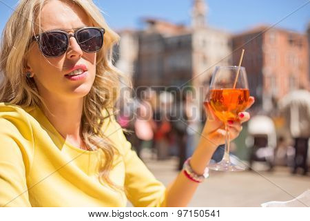 Woman sitting in outdoor cafe and drinking Aperol Spritz cocktail