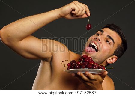 Man eats red fresh cherry