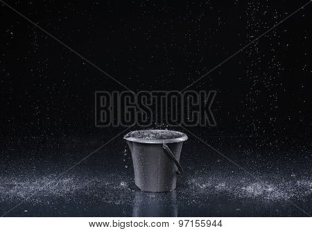 Bucket with water drops on dark background