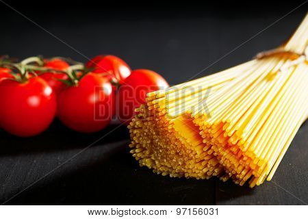 Raw pasta and tomatoes on black table close-up
