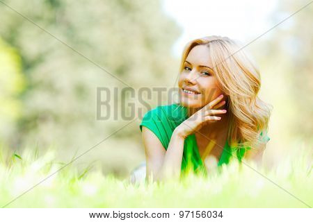 Happy young woman lying on grass